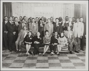 Lee in group photo. He is standing behind couch between seated woman and man on her left.